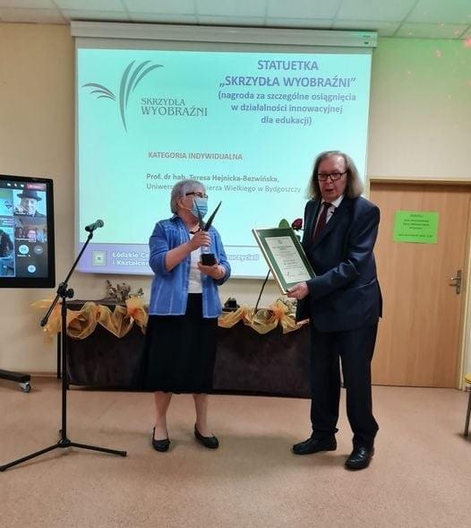 Prof. Hejnicka-Bezwińska (w maseczce ochronnej) odbiera statuetkę Skrzydła Wyobraźni podczas gali rozdania