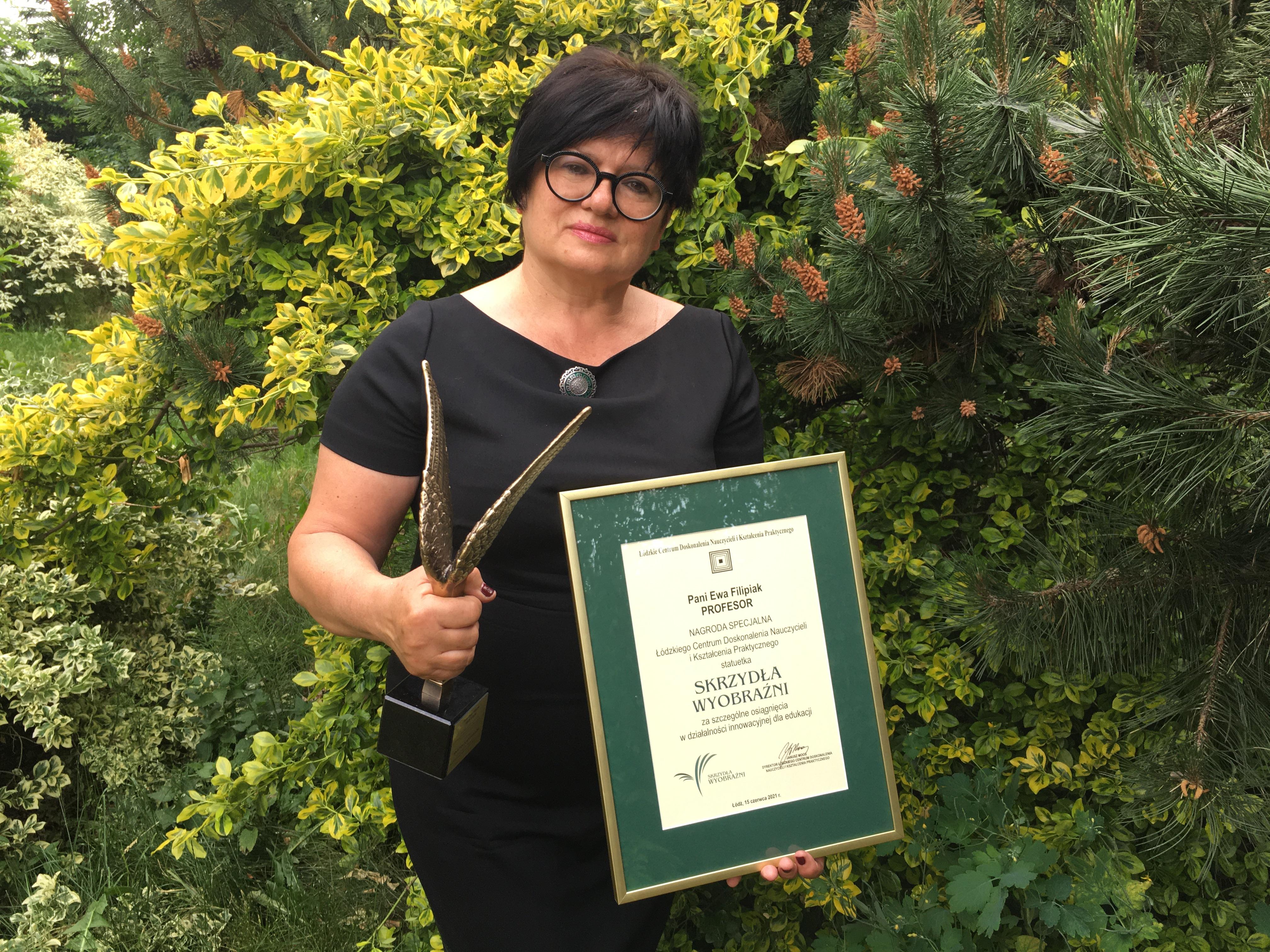 Prof. Ewa Filipiak w czarnej sukience i okularach dzierży w dłoniach statuetkę i dyplom